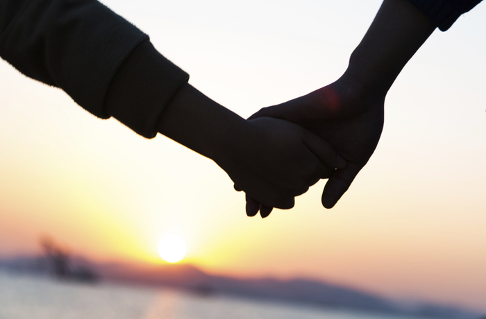 A couple holding hands in front of the sea at sunset.